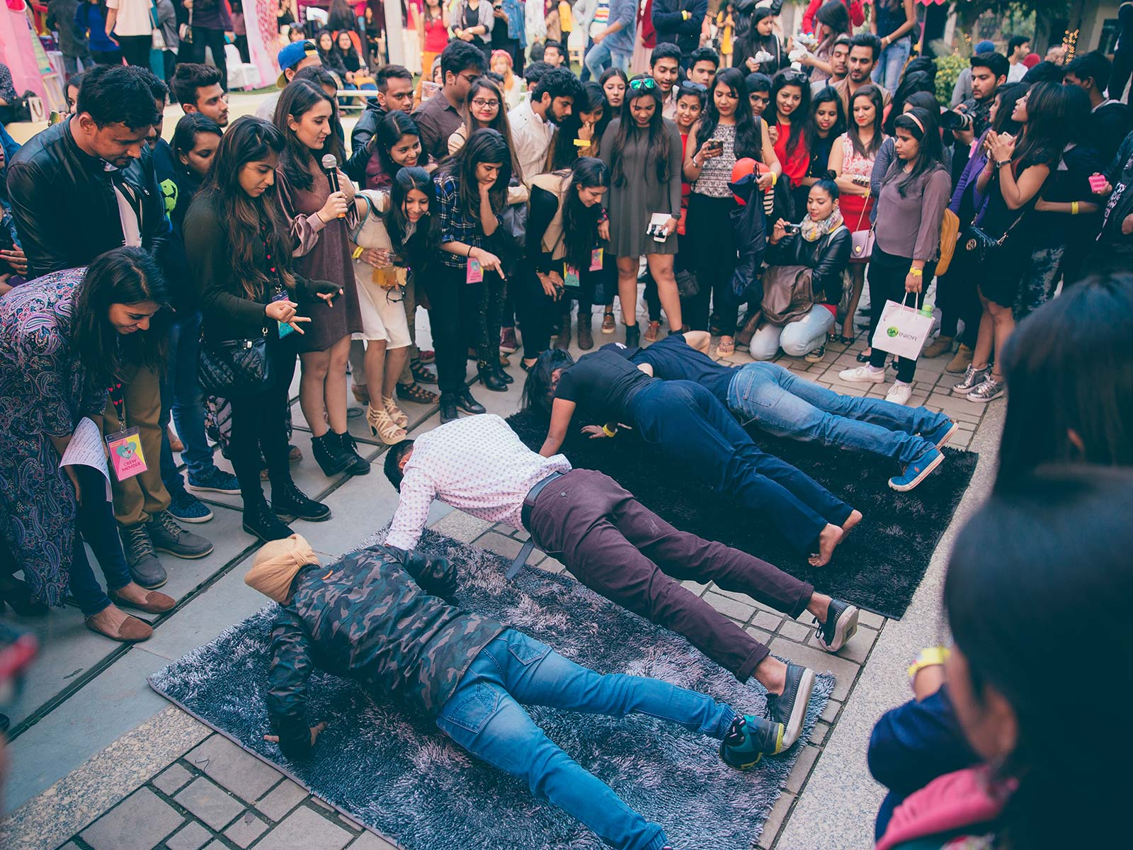 Boys participate in the Plank task at the POPxo Love Fest while their friends cheer them on