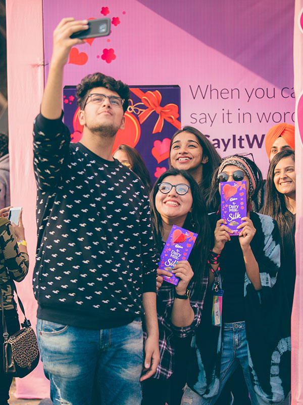 Guests take selfies at the Cadbury booth at the POPxo Love Fest